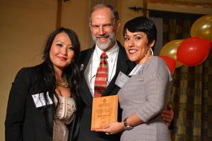 Two women and a man receiving an award